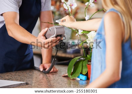 Mobile Payment with smartphone at checkout in nursery retail store - stock photo