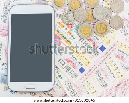 Mobile phone and coins on Thai lottery tickets - stock photo