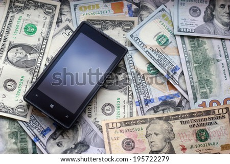Mobile phone and dollar bank notes - stock photo