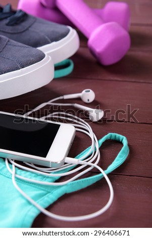 Mobile phone and earphones with set for sports on wooden table, closeup