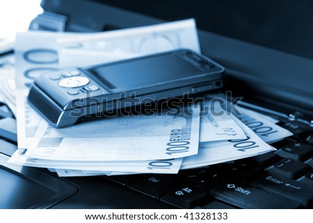 Mobile phone and euro banknotes on laptop, toned blue - stock photo