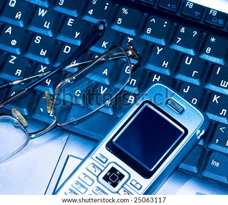 Mobile phone and glasses on computer keyboard (business conception) - stock photo