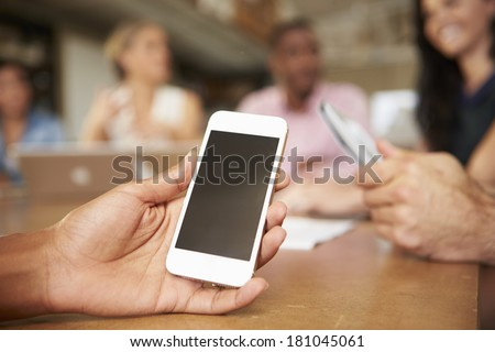 Mobile Phone Being Used By Architect In Meeting - stock photo