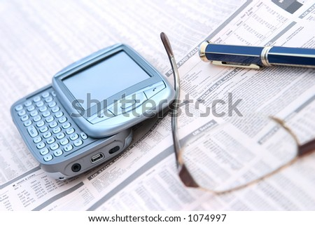 mobile phone, glasses, and a pen on top of a financial newspaper. Shallow Depth Of Field. - stock photo