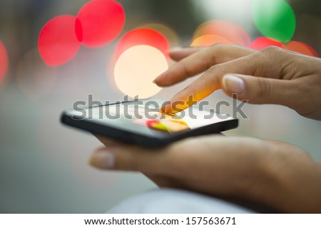 Mobile phone in a woman's hand, night, city ??of Light background, sms, message, e-mail
