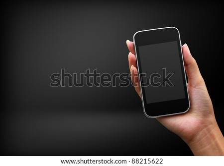 Mobile phone in hand on black background - stock photo