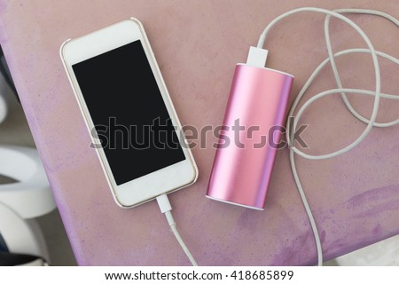 mobile phone in plastic case plugin to a power bank charger through a charging cable, on old pinkish purple outdoor plastic table - stock photo