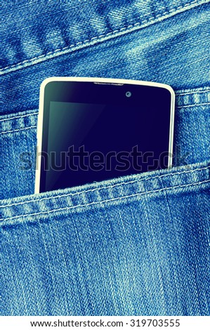 Mobile phone is in the pocket blue jeans.