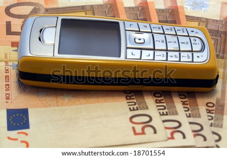 Mobile phone laying on four 50 Euro notes - stock photo