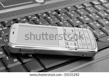mobile phone lies on the laptop keyboard - stock photo