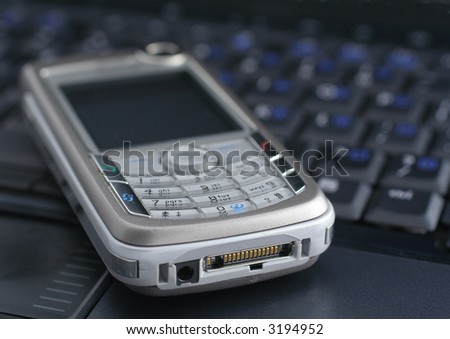 mobile phone lying on a laptop