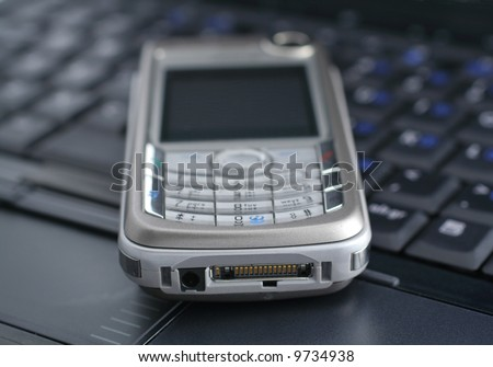 mobile phone lying on a laptop keyboard - stock photo