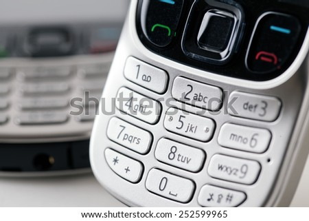 Mobile phone number keypad close up with a second handset in the distance out of focus - stock photo