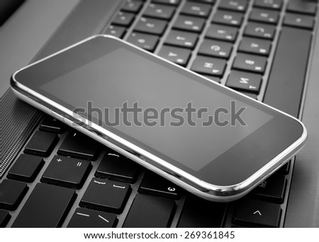 mobile phone on a laptop - stock photo