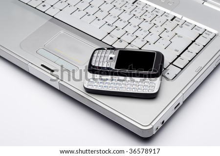 Mobile phone on a laptop.