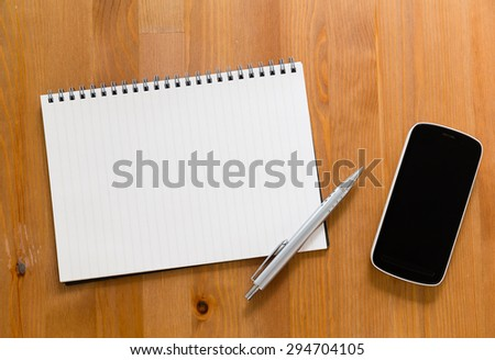 Mobile phone on desk with blank handbook for input something - stock photo
