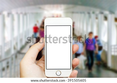 Mobile phone on hand and people walk in background. - stock photo