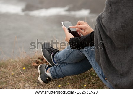 Mobile Phone on Human Hand by the Beach - stock photo