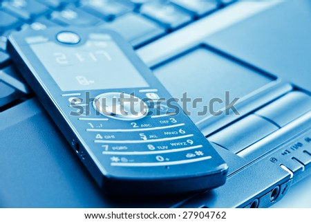 mobile phone on laptop keyboard with shallow depth of field - stock photo