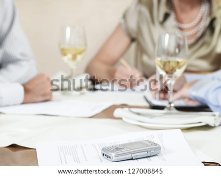 Mobile phone on table with people writing notes in the background