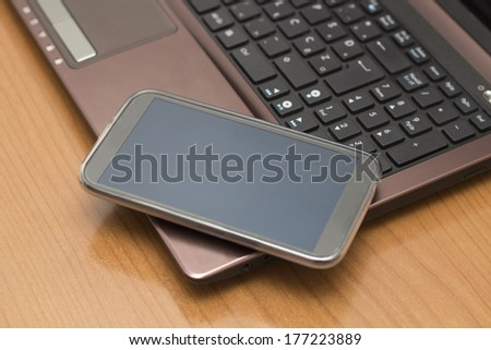 Mobile Phone on the Laptop - stock photo