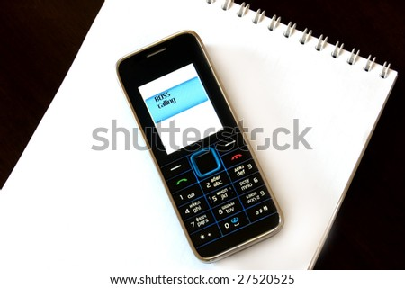 mobile phone on white notebook - stock photo