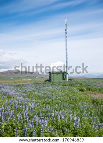 Mobile phone telecommunication radio antenna tower in a summer blooming field. Concepts: communication, environment, nature, electromagnetic pollution. Iceland, Europe. - stock photo