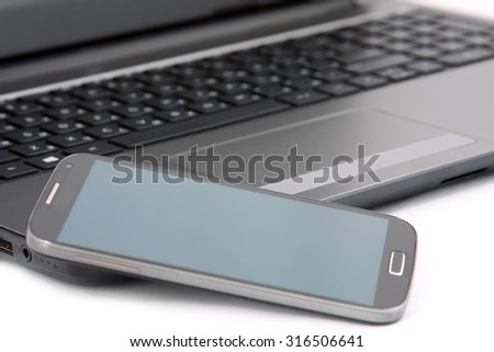 mobile phone, touchpad and keyboard of the notebook on white