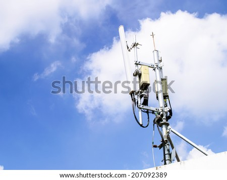 mobile phone transmitter antenna on blue sky background - stock photo