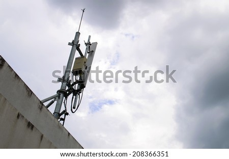 mobile phone transmitter antenna on sky with many clouds - stock photo