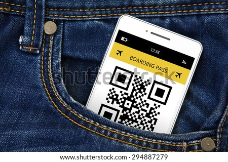 mobile phone with boarding pass in jeans pocket. focus on mobile phone. - stock photo