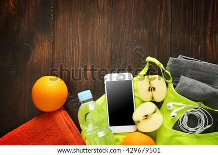 Mobile phone with towels and fruits on wooden background - stock photo