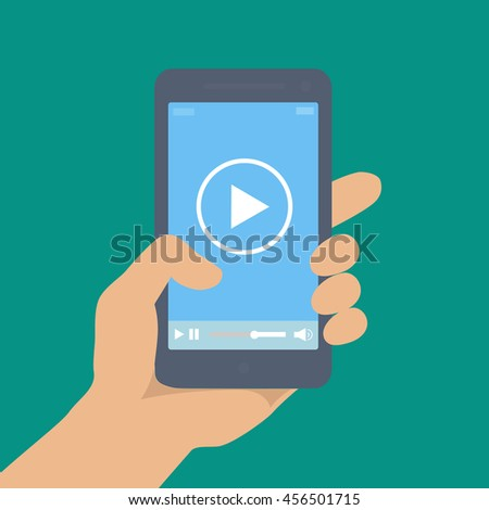 Mobile phone with video player on the screen in a human hand - stock photo