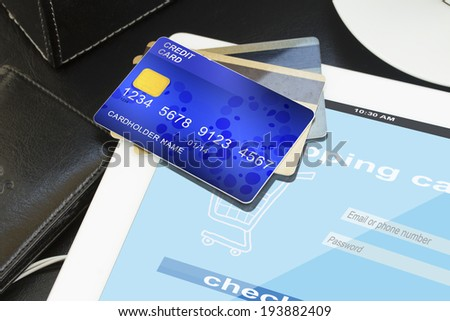 mobile shopping  -pile of credit cards with virtual shop on screen of tablet - stock photo