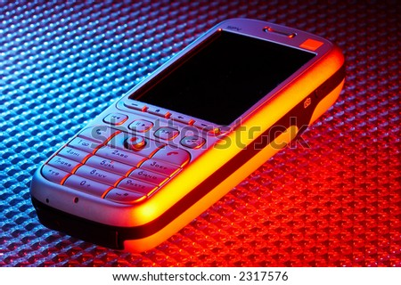 Mobile smart phone on high tech colour background - stock photo
