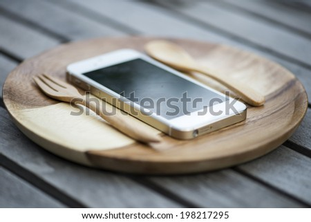 Mobile smart phone served on wood plate. Concept - stock photo