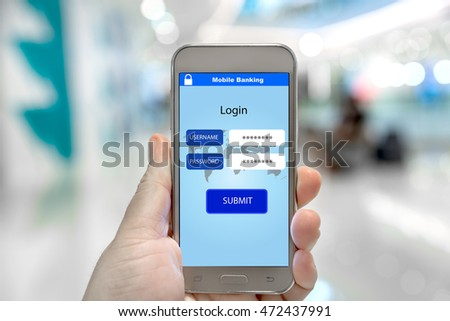 Mobile smart phone with mobile banking log in page holded by hand in shopping mall.