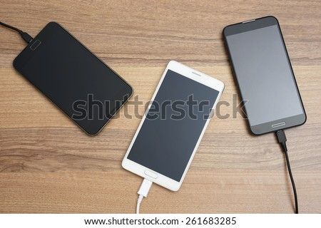Mobile smart phones  charging on wooden desk - stock photo