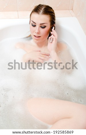 mobile spa communication: image of beautiful sensual young woman sexy girl having fun talking on cell phone & relaxing in foam bath happy smiling - stock photo