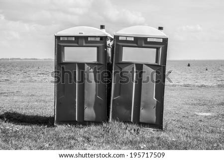 Mobile toilet on a beach. Black and white image  - stock photo