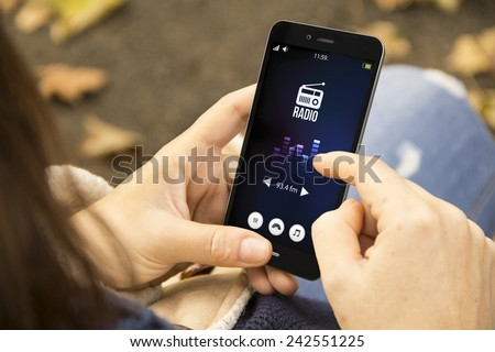 mobility and modern lifestyle concept: young woman listening radio app on the smartphone at the park - stock photo