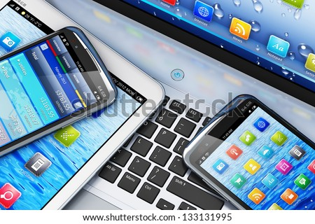 Mobility and modern telecommunication concept: macro view of tablet computer and touchscreen smartphones with colorful interfaces on laptop notebook PC - stock photo