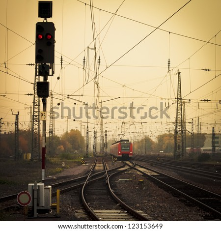 Moble photography lo-fi styled image of a red commuter train on an urban railway track with confusing lines and overhead cables and a red signal light - stock photo