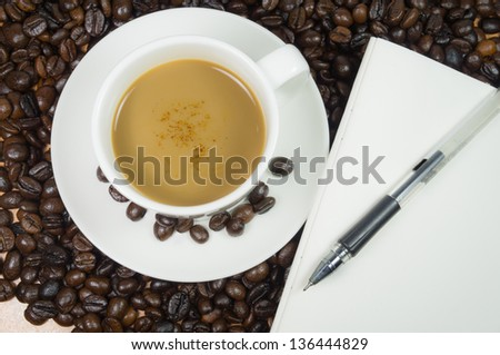 Mocha coffee with notebook and bean in background