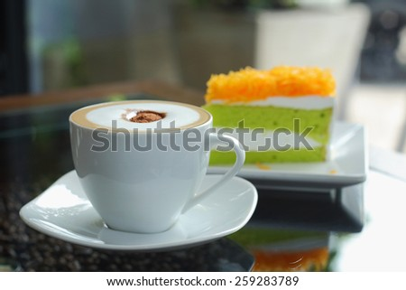 Mocha in white coffee cup and Foythong Cake or Gold Egg Yolks Thread Cake in the Coffee Shop - stock photo
