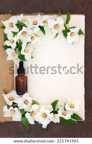 Mock orange flower border with essential oil bottle on a natural hemp notebook over brown paper background. Philadelphus. - stock photo