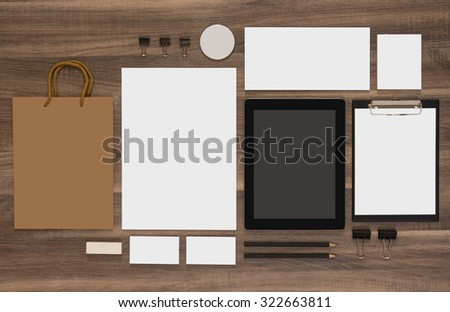 Mock-up business branding template with shopping bag, mobile tablet and envelopes. Natural wooden background. - stock photo