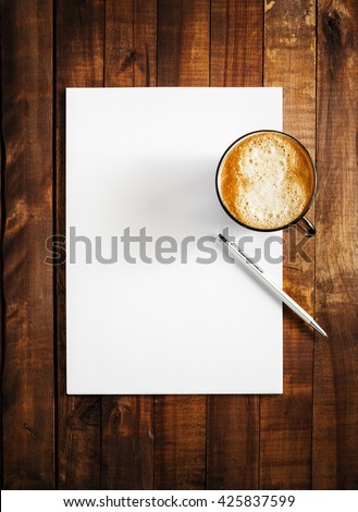 Mock-up for branding identity on vintage wooden table background. Blank letterhead, coffee cup and pen. Mock-up for design presentations and portfolios. Top view. - stock photo