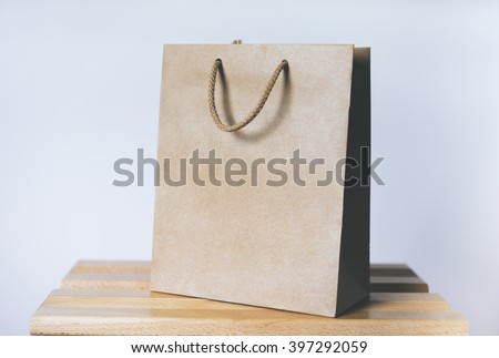 Mock-up of blank craft package, mockup of brown paper shopping bag with handles on the white background - stock photo