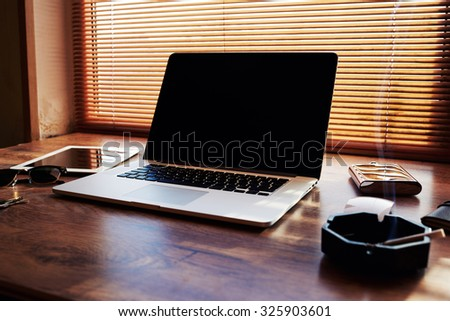 Mock up of business person desktop with open portable laptop computer with blank copy space for text message or information content, net-book with digital tablet lying on a office table  - stock photo